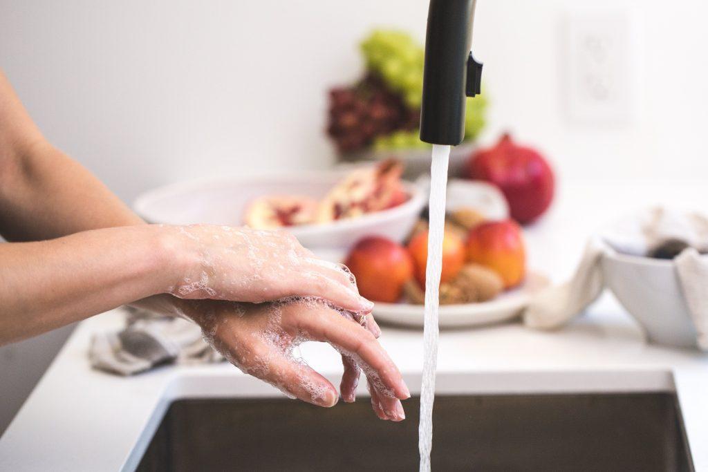 woman washing hands at sink