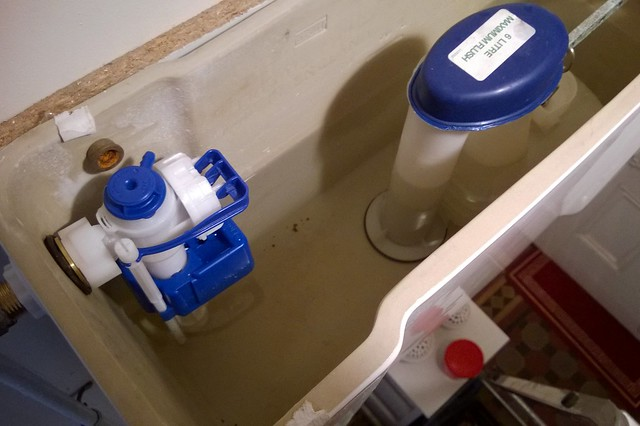 Picture of a flush valve and fill valve to help show what parts may need replacing with toilet tank leaking into the bowl.