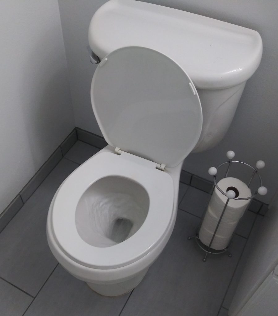 A toilet in the middle of flushing.