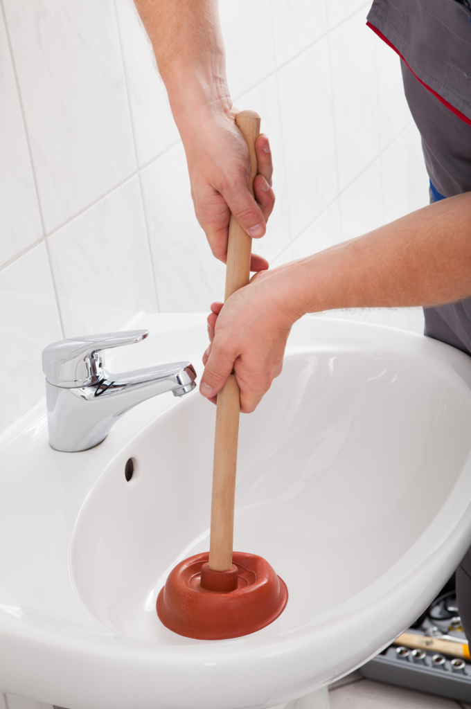 person unclogging a sink with a plunger