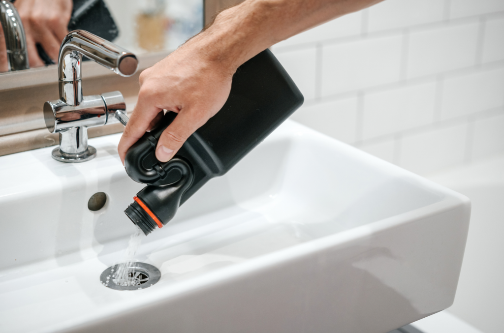 someone pouring liquid drain cleaner into a sink drain